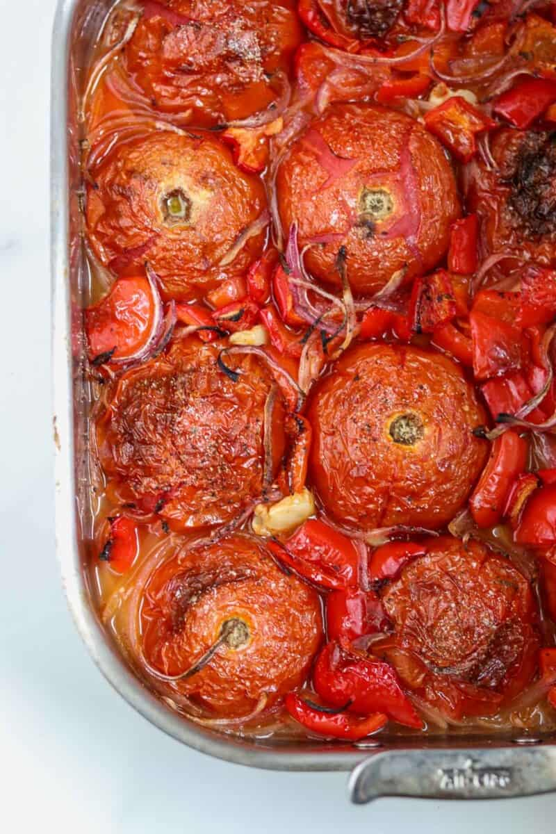Roasted tomatoes, peppers and onions in a roasting pan.