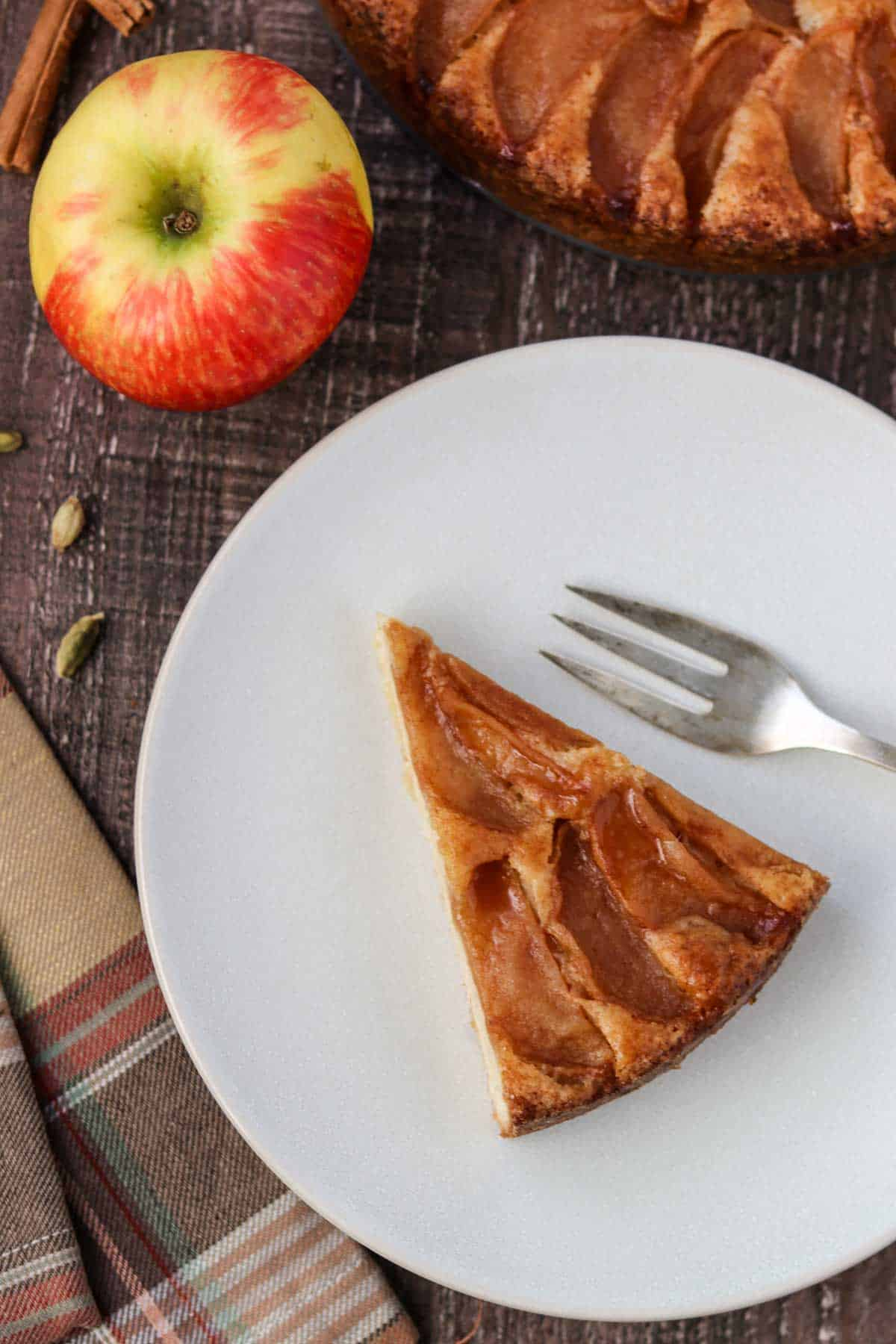 Slice of Swedish Apple Cake on a plate next to a fork, apple and plaid napkin.