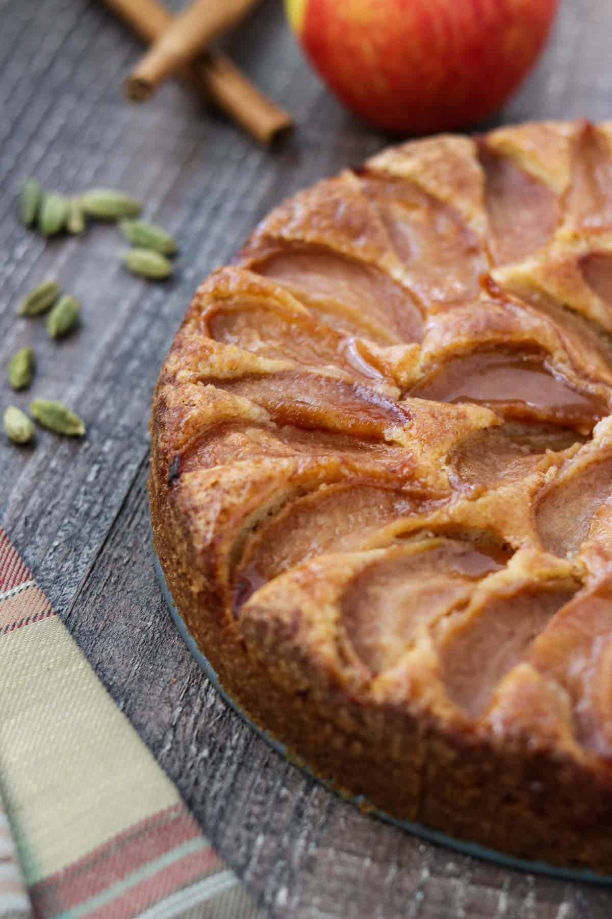 Side view of Swedish Apple Cake with cardamom pods and a plaid napkin.