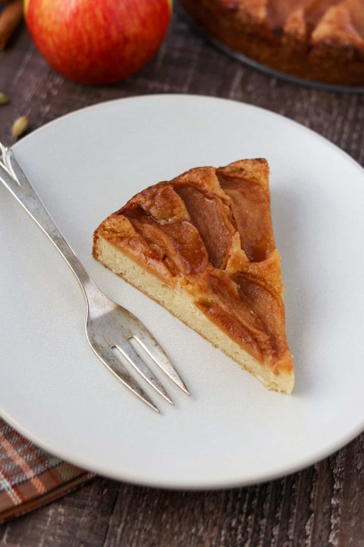 Slice of Swedish Apple Cake on a plate next to a fork.