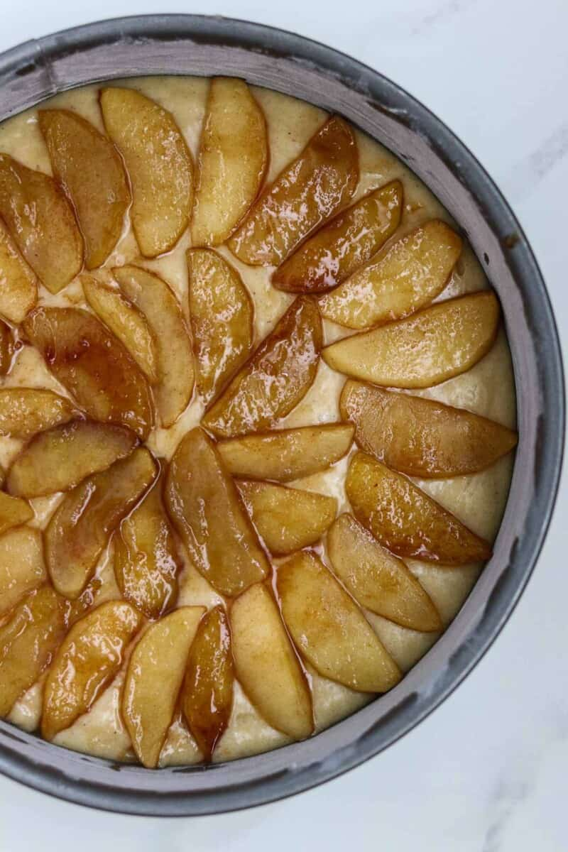Unbaked apple cake in a pan.